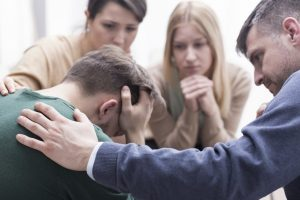Sad man with head in hands. Coworkers standing by offering support.