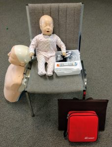 First aid class individual workstation with CPR manikins, AED trainer and first aid supplies